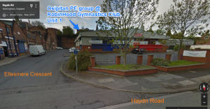 "Photo, labelled with where things are. A road going ahead is labelled Ellesmere Crescent. A road going to the right is labelled Haydn Road. On the corner is a car park, and at the back of a car park is a big warehouse. It's mostly grey. The left half of the warehouse is partly blue, and the right half is partly red. On the blue half, a sign reads ""ROBIN HOOD"", and some smaller letters which can't be read on the photo. A label on the photo points to that part of the warehouse, saying ""Osipitan PE group @ RobinHood Gymnastics Club. Unit 1."""