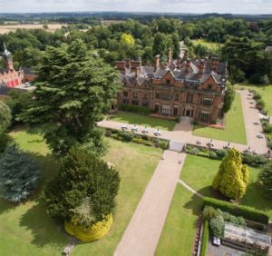 Photo: a large red-brick hall with pointy roofs and tall chimneys is viewed from above, as if from an aeroplane. It stands within formal lawns and is surrounded by woodland. A further courtyard can be glimpsed to the left of the picture. The horizon can be seen in the distance.