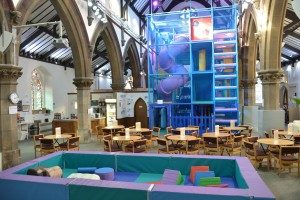 Photo: interior of a church, with pillars and arches visible. Instead of pews, there are chairs and round tables set out café style. In the foreground is a toddler play area, a sort of gigantic soft tray with soft shapes in it. At the far end is a large play structure, with four tiers of blue framework. A ladder can be seen at the front, and a curving tubular slide can be seen inside it.