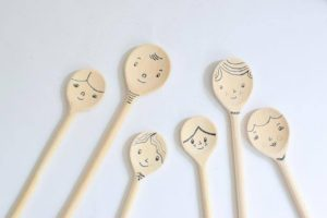 Six wooden spoons each have a smiley face drawn on their round end, and are arranged on a white background like a family of smiling spoons.