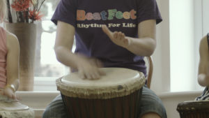"A child's hands can be seen playing an African-style drum. Part of the child's t shirt can be seen. The t shirt has in colourful letters ""BeatFeet"". Below the ""BeatFeet"" logo is the phrase ""Rhythm For Life""."
