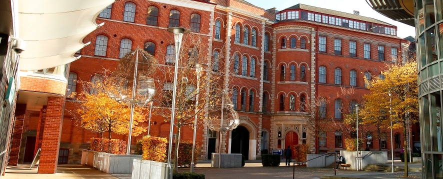 Photo of Adams Building, New College Nottingham. It's a large brick building which used to be a lace mill. In front of it is a courtyard. The view is across the courtyard, showing a little bit of nearby buildings as well.