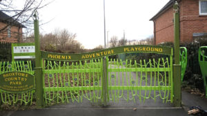 "A path ahead is blocked by a bright green metalwork double gate made of plant-like shapes. Above the gate is a decorative metal sign reading ""Phoenix Adventure Playground"". To the right is an opening where a person could walk through but bike handlebars would be stopped by the metal frame. The edges of two houses show, one each side of the path. Trees are silhouetted in the distance. A less decorative sign in the background labels it as ""Broxtowe Country Park and Phoenix Adventure Play Area"", and shows some icons, but the icons are too far away to decode properly by this photo."