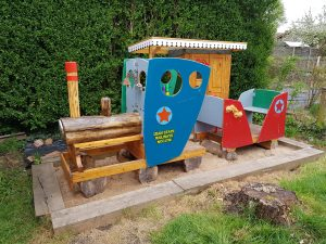 A colourful play train (one engine, one carriage which would seat four small children) made partly of treetrunks and partly of flat material, on a sandy base. In the background is a tiny station platform. It's actually in the garden of the people who run the Ex Libris booksales, and is known as the Ex Libris Express.